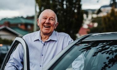 Senior gentleman smiling next to his car with driver door open