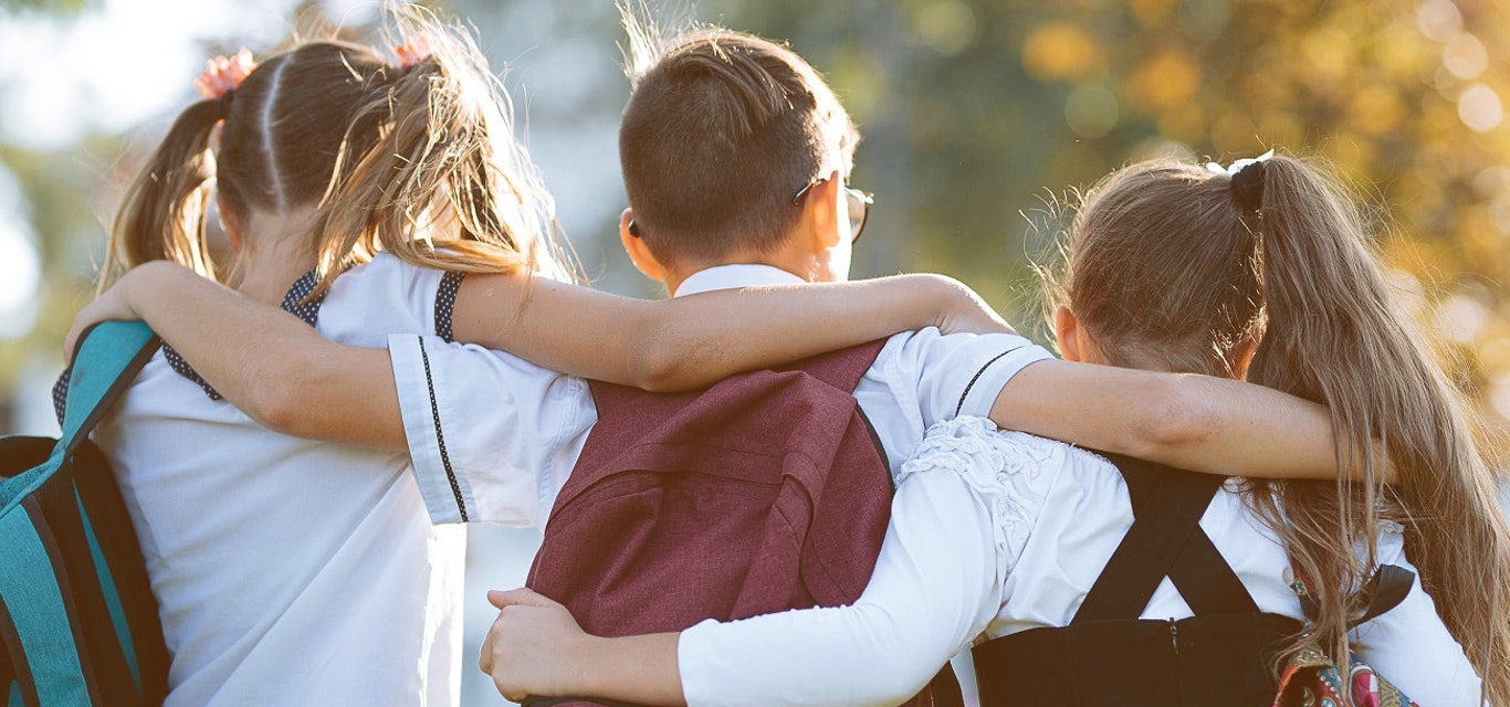 School children with their arms around each other