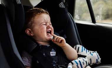 Crying toddler in car seat in a hot car