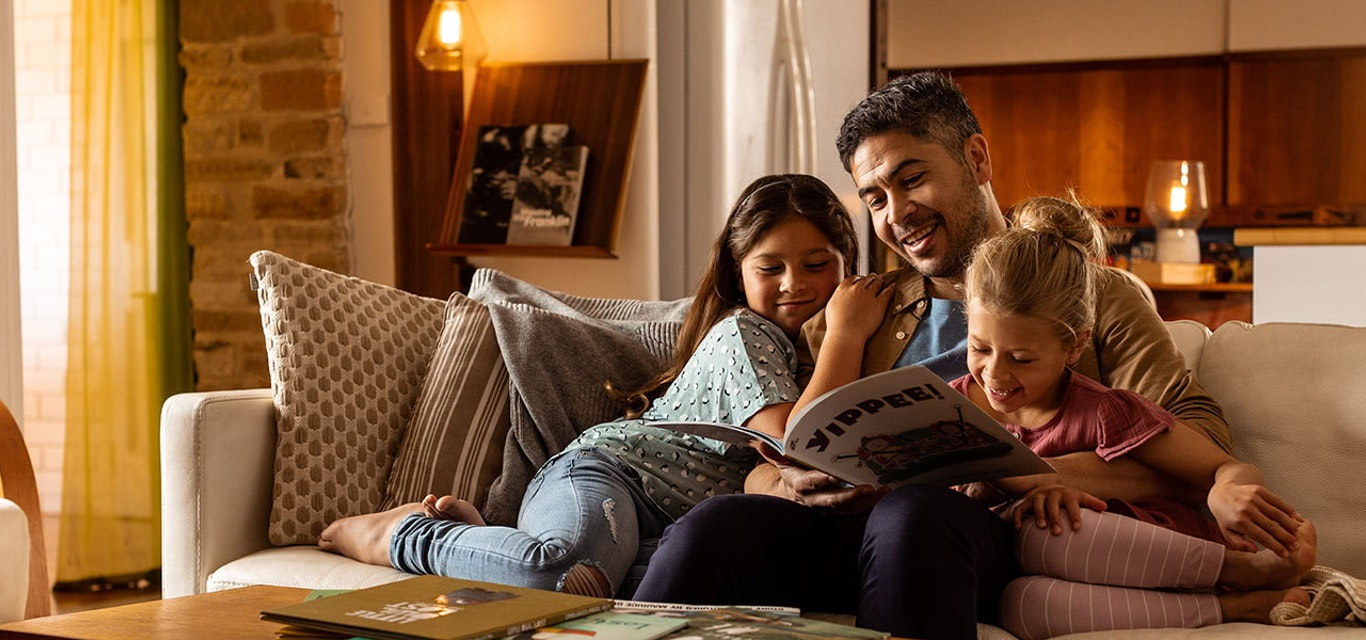Family reading on a couch.