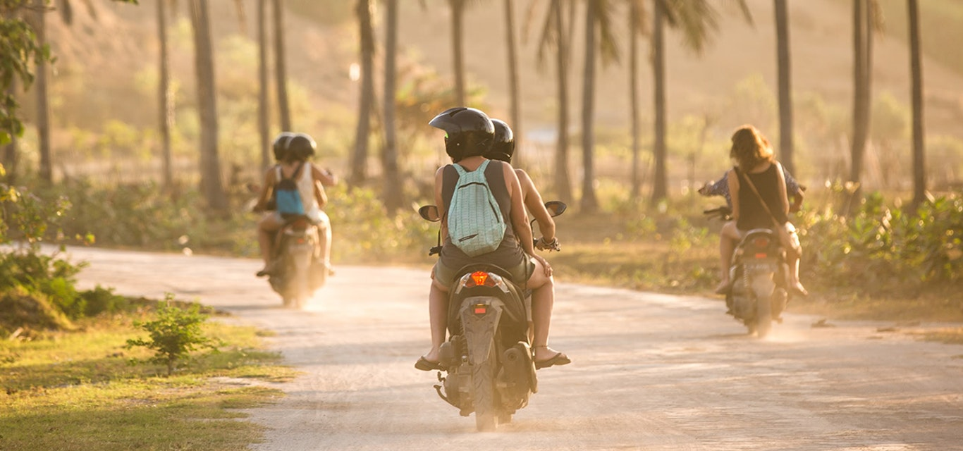 Motorbikes riding along a dusty road on a tropical island