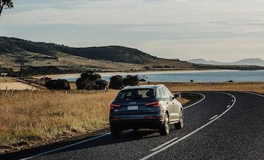 Audi SUV driving along coastal road