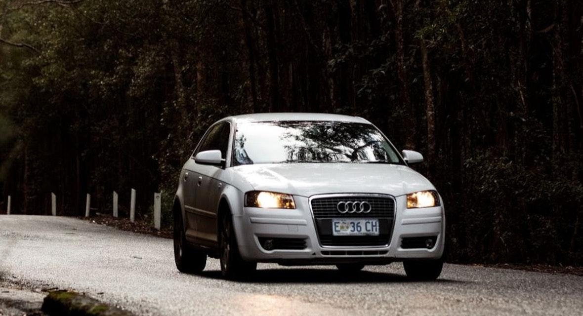 Audi sedan driving a rural road