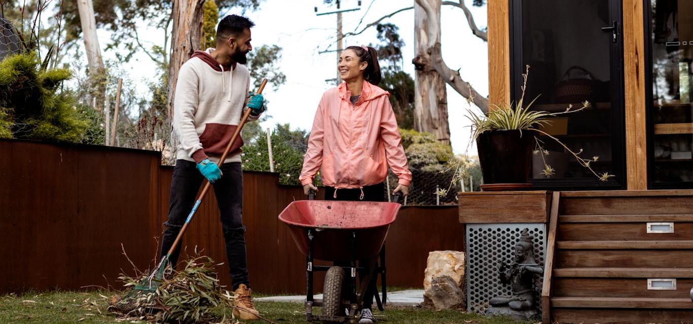 A man and woman perform garden work with a rake and wheelbarrow