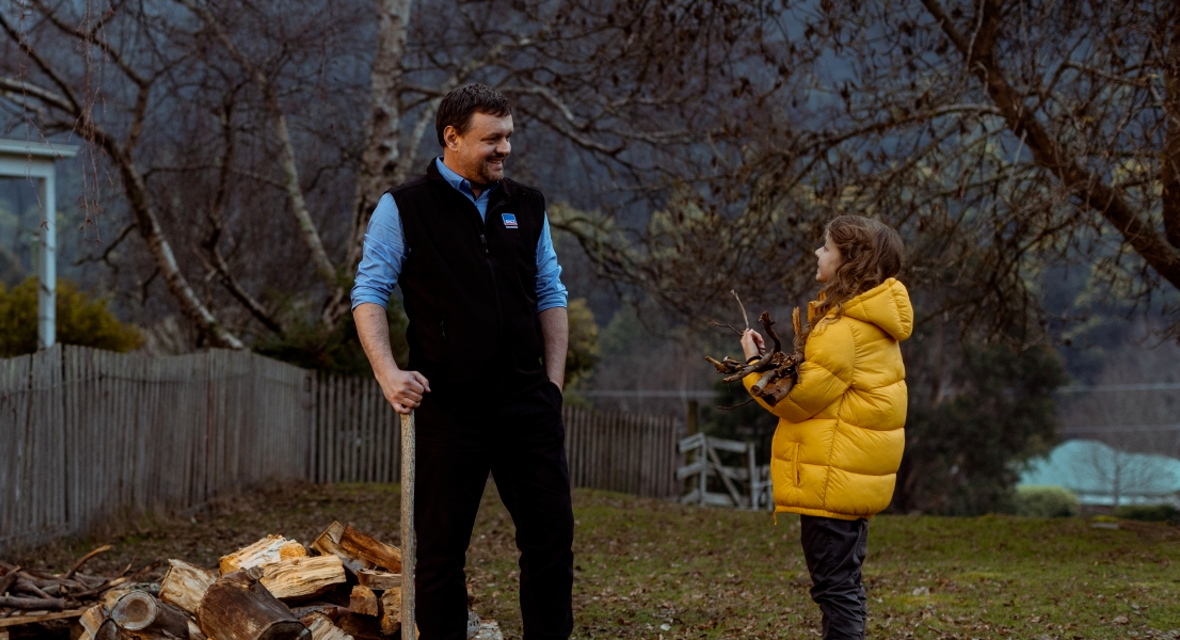 TV commercial screen cap - RACT Insurance staff member outdoors with axe chopping wood