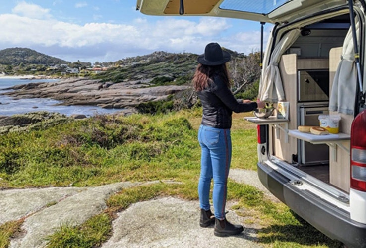 Young lady prepping some food at the back of her Apollo campervan