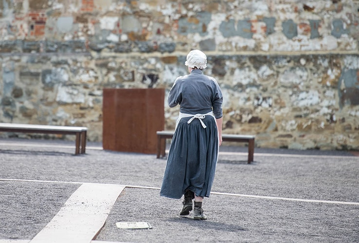 A woman dressed as a convict walks across a courtyar