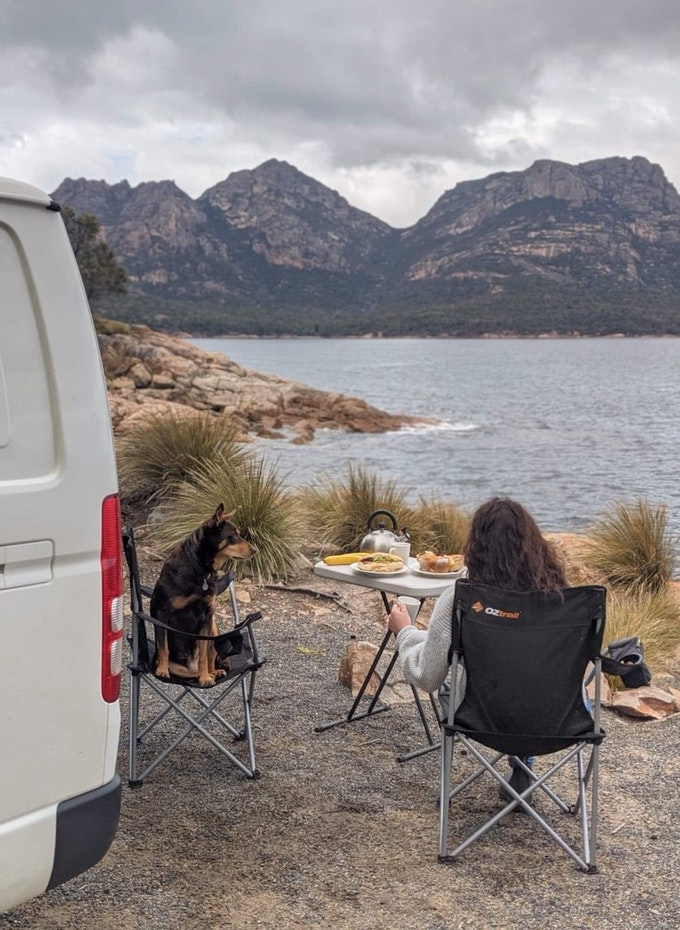 Young lady and her dog enjoying a picnic outside their campervan at Coles Bay