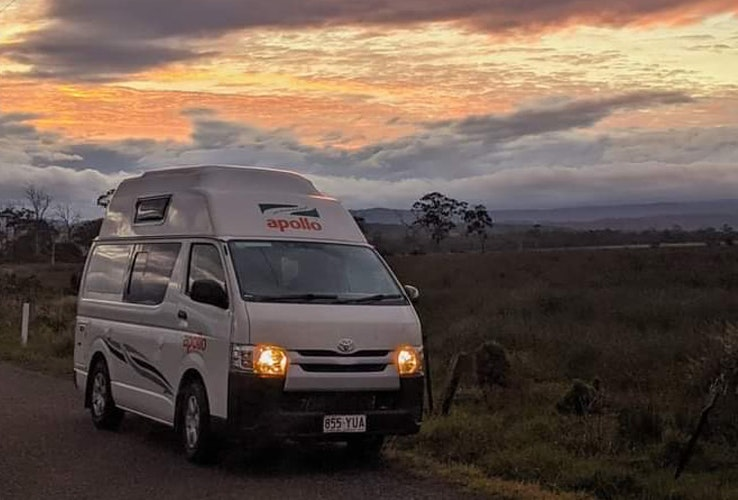 Apollo campervan at dusk with its headlights on