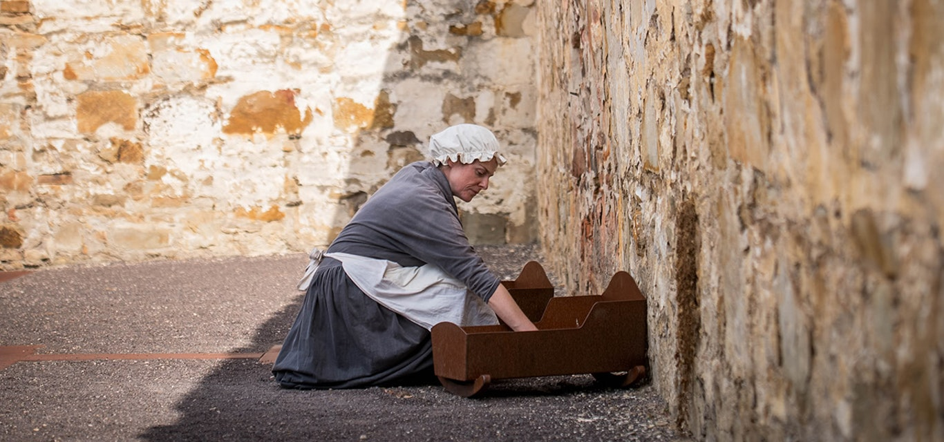 woman dressed as a convict kneeling over a wooden crib