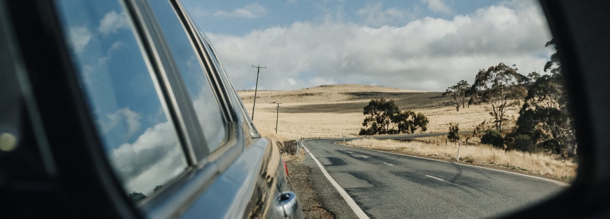Country view of road from car side mirror