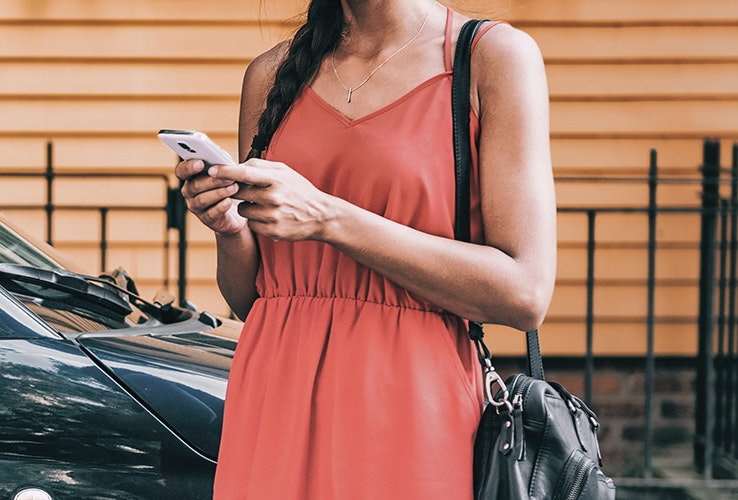 Young lady in red dress looking at her mobile phone