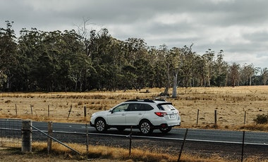 White Subaru Outback driving along a rural road