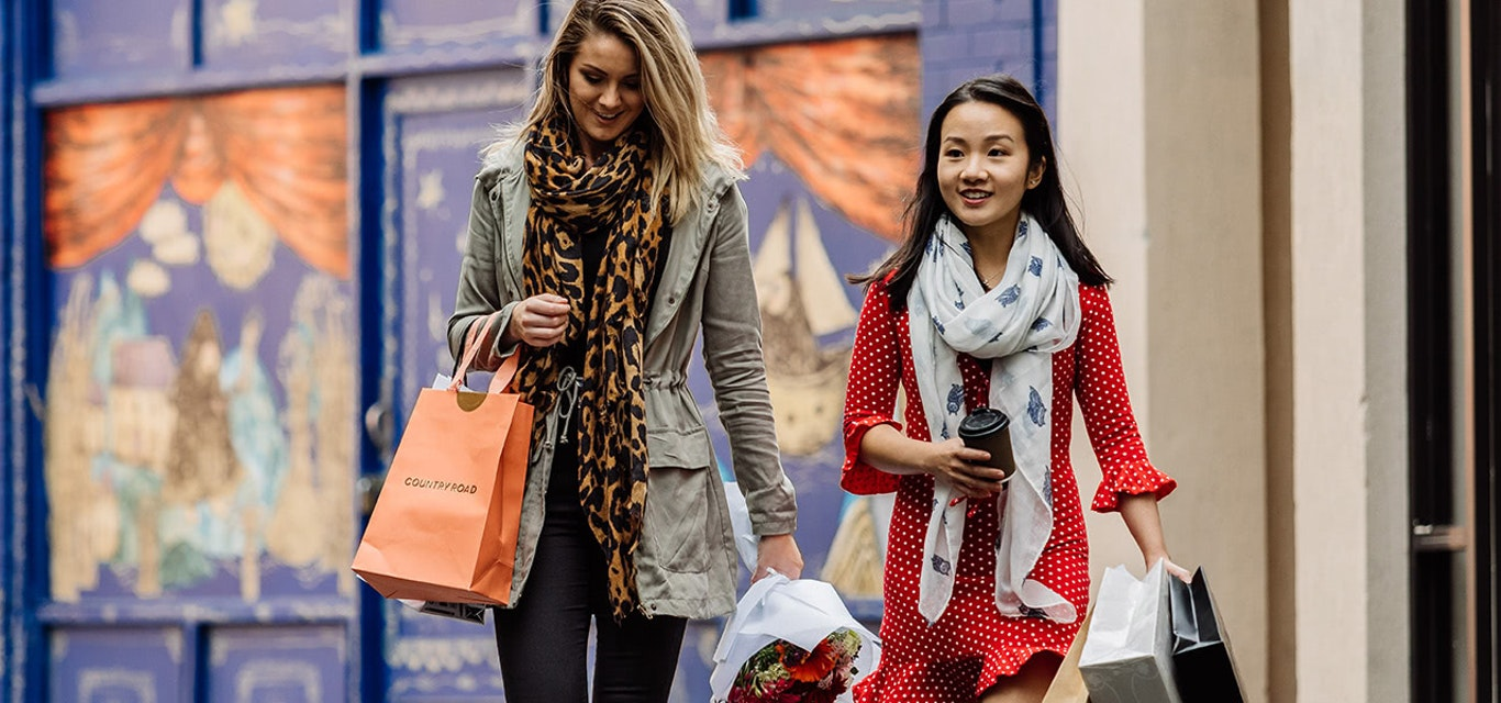 Young ladies on a shopping spree carrying lots of retail bags