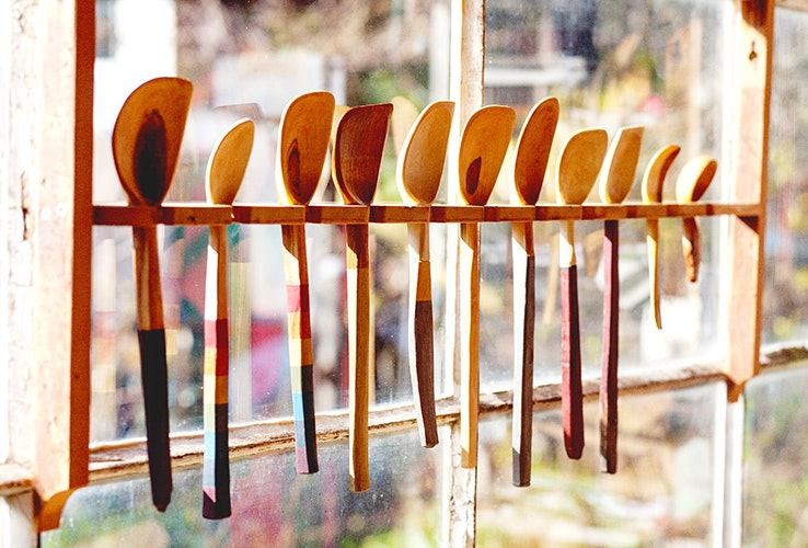 Hand-crafted wooden spoons of differing shpaes and sizes hanging in a wooden rack
