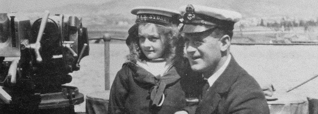 Young girl and sailor pose for photo on the HMAS Sydney
