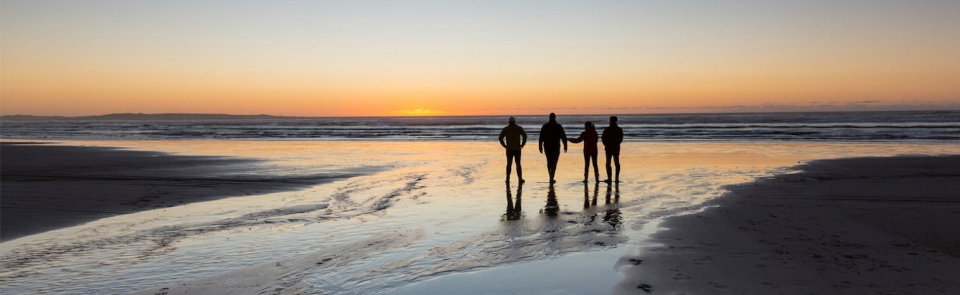 Four silhouettes on a beach at sunset