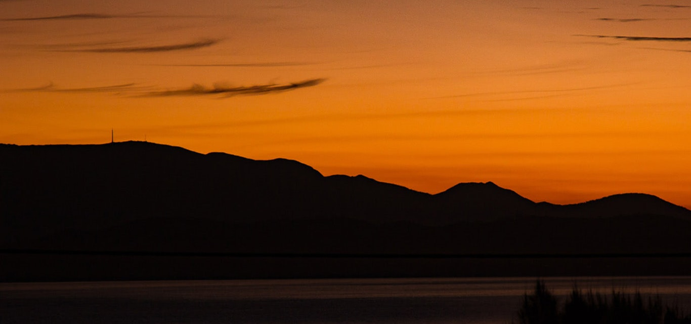Sillhouette of Mount Wellington and Hobart in front of an orange sky
