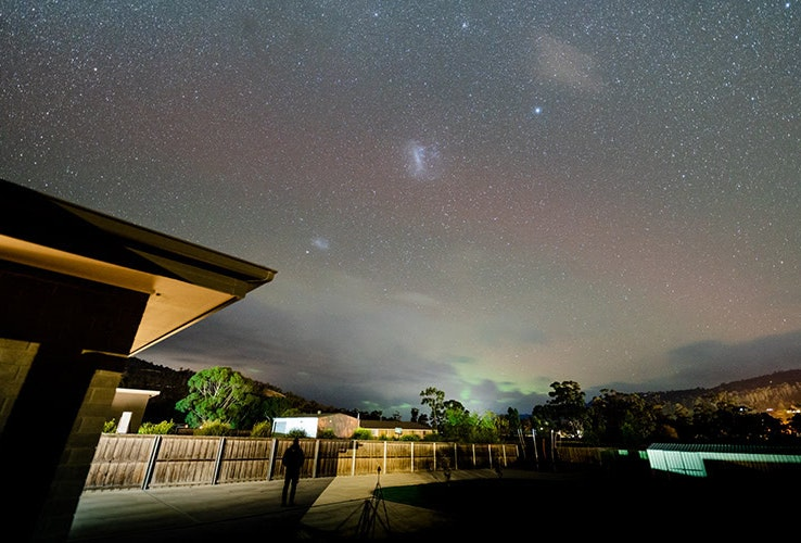 View of Aurora Australis and starry sky from a backyard