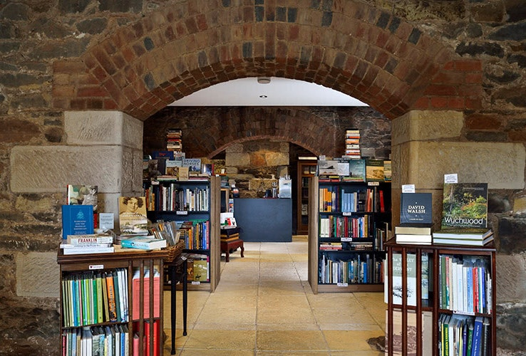 A view of many books on shelving through a rustic brick and sandstone arch