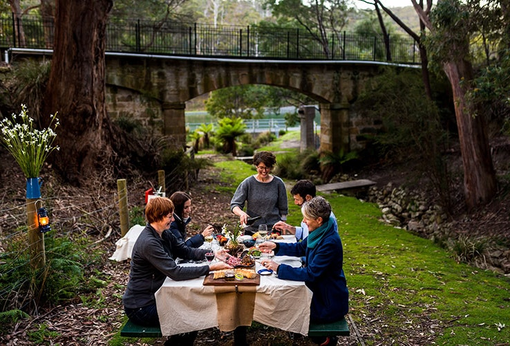 A small group dining outside on a picnic table with tablecloth enjoying cheese and wine