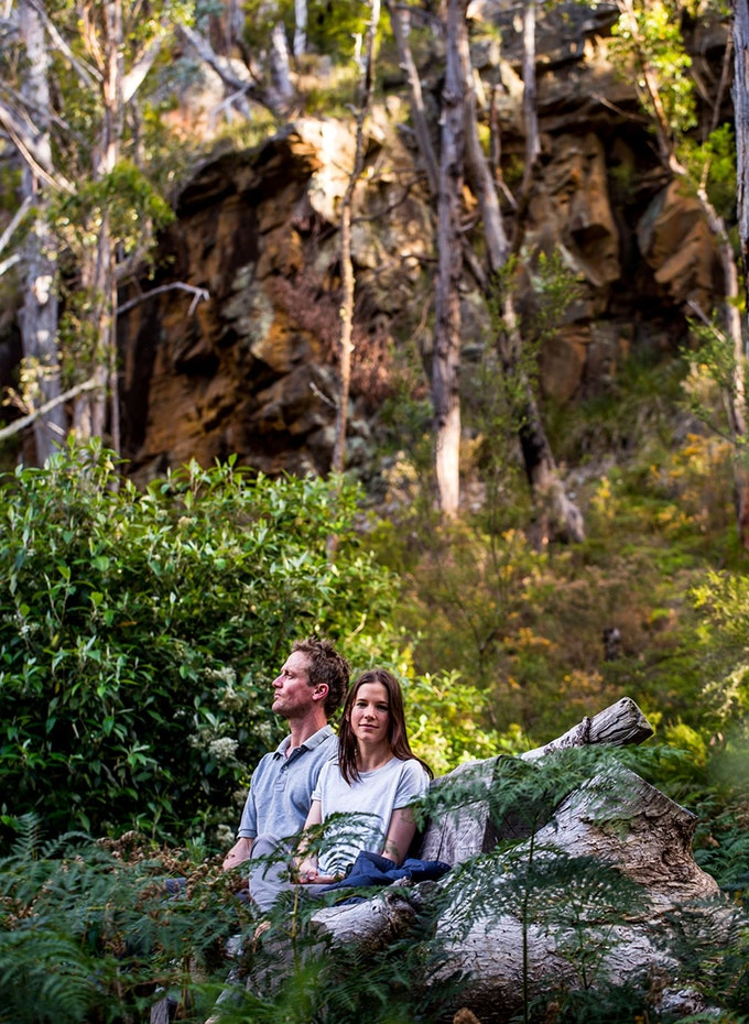 Young couple relaxing on a large fallen log enjoying the outdoors