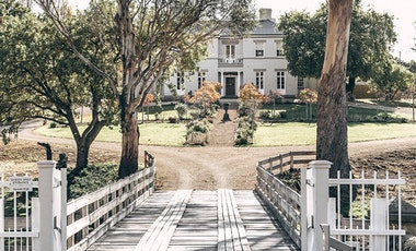 A view of Prospect House through trees and across the entry bridge