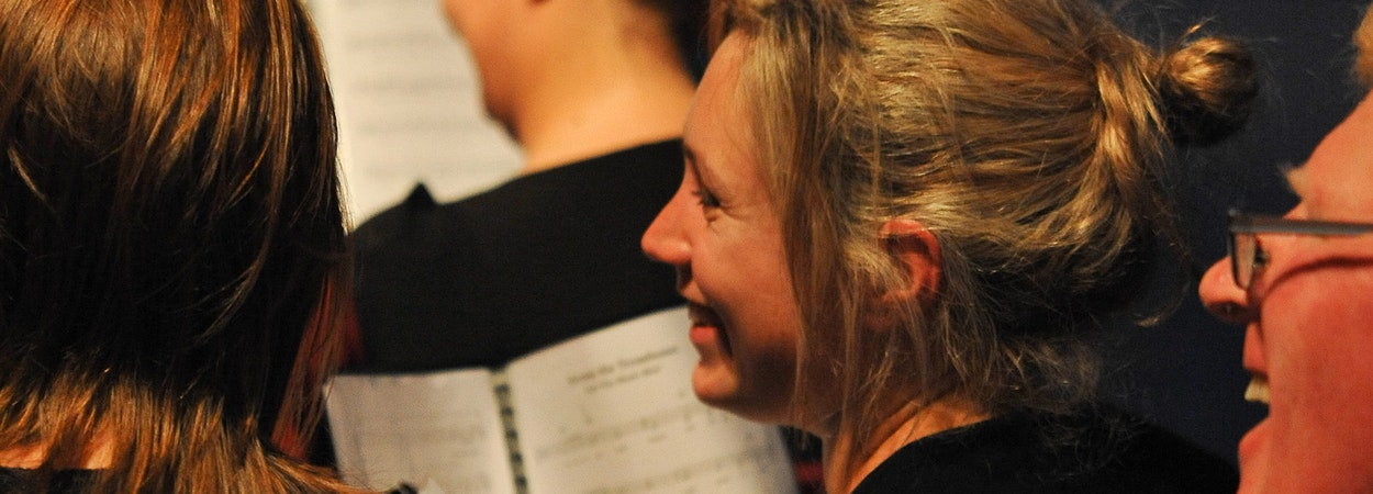 A smiling girl singing in a choir
