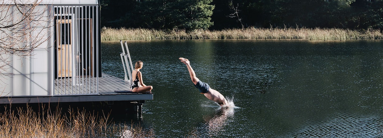 A man dives into a still lake