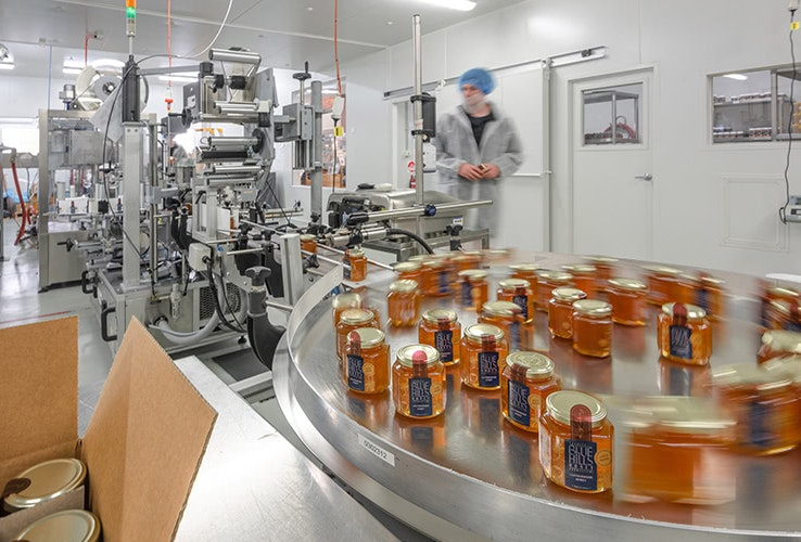 Jars of honey being manufactured