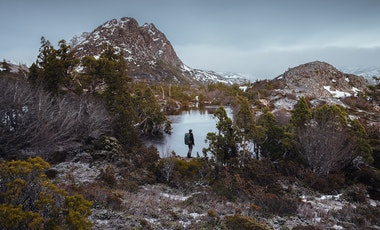 A man stands at the edge of a lake at Cradle Mountain