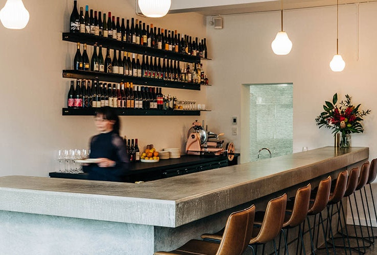 Waitress behind the bar in an empty wine bar