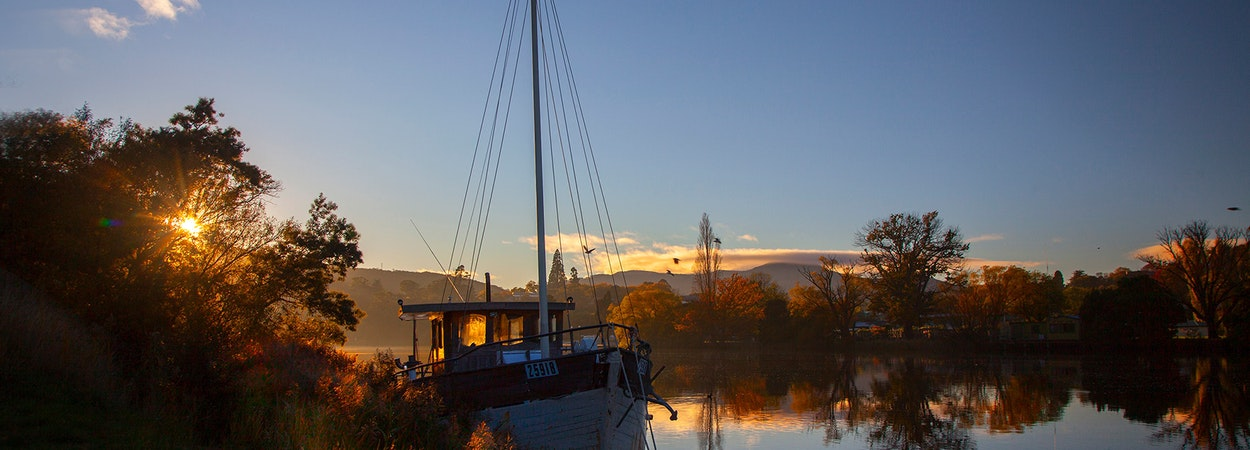 Boat on river during sunrise.