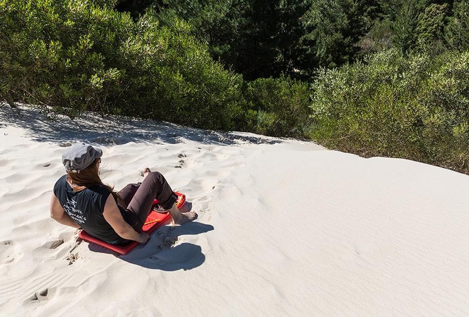 Tobogganing down Henty Dunes in Tasmania