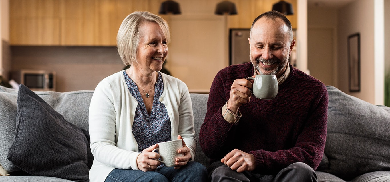 Smiling couple enjoying a coffee at home