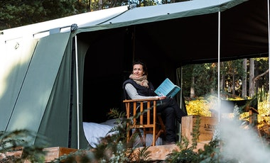 A woman reads a book in a tent on Bruny Island