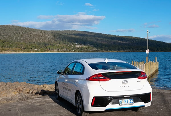 White Hyundai electric vehicle parked next to jetty and water