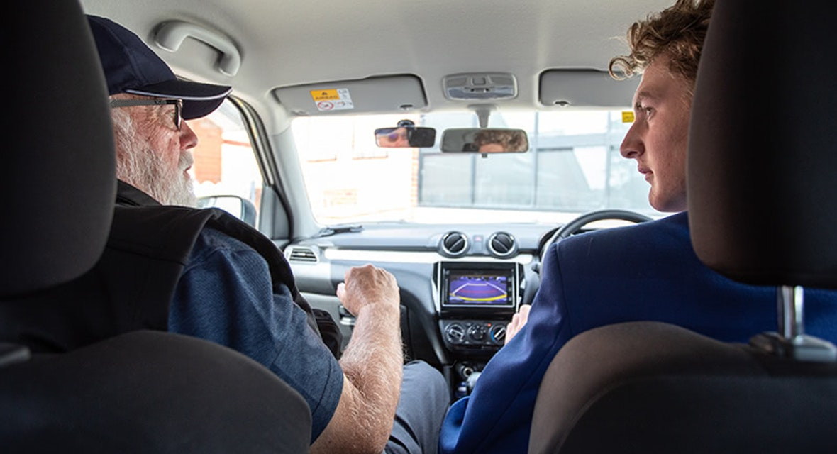Student driver and driver instructor sitting in a car