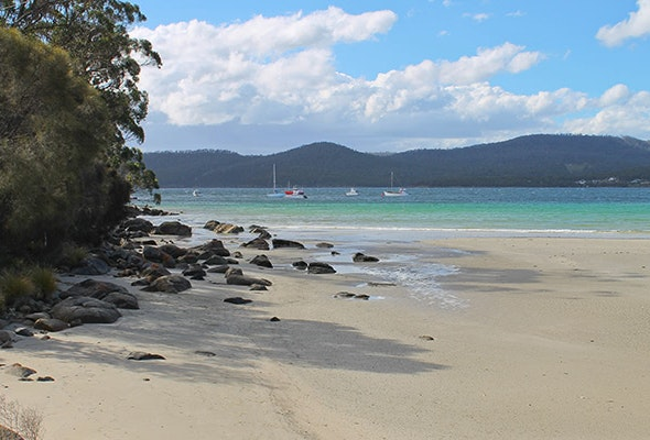 Secluded beach with boats on river in background