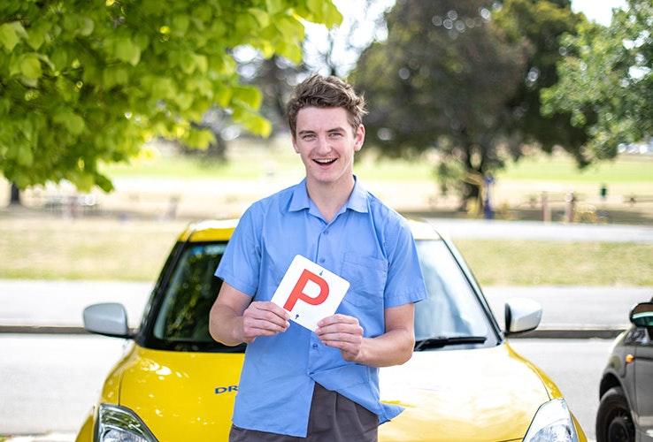 Teenage boy in school uniform holding up a P plate