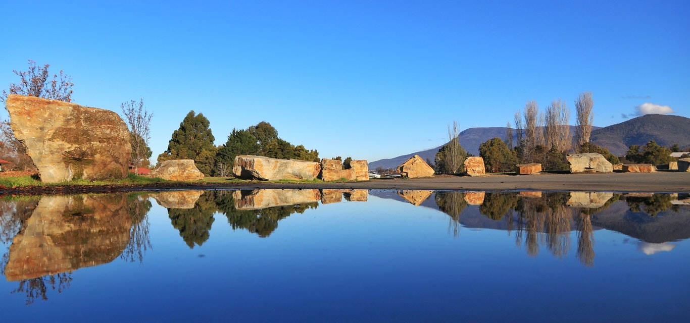 Perfect reflection in a lake of Mount Wellington and positioned boulders