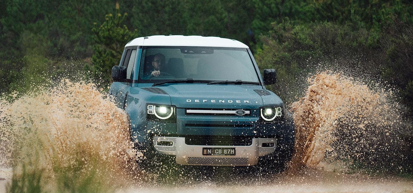Land Rover driving through a creek