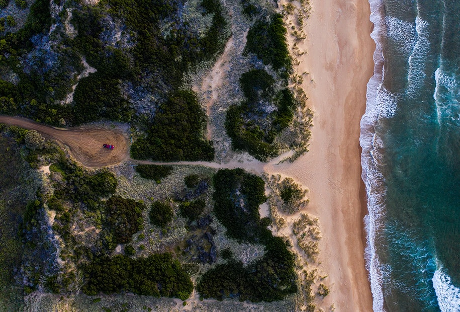 Aerial view of waves, beach, bush and the red Mazda BT-50