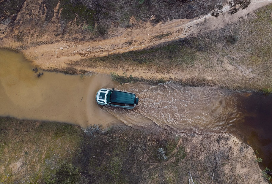 Landrover Defender driving through muddy water