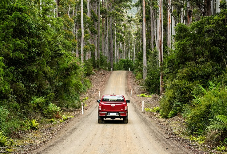 Red Mazda BT-50 ute driving down a dirt road