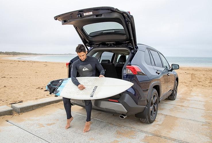 Gentleman sitting in the back of new Rav 4 waxing surfboard.