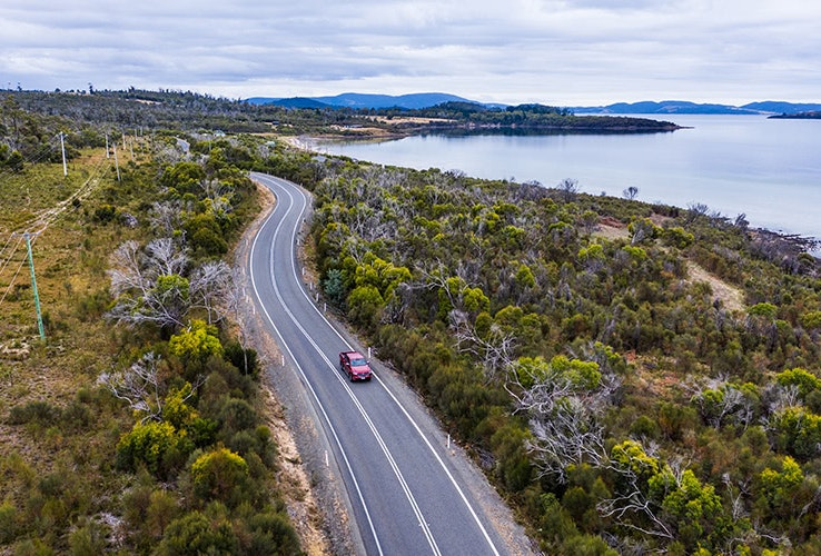 Aerial view of red Mazda BT-50 driving down coastal road