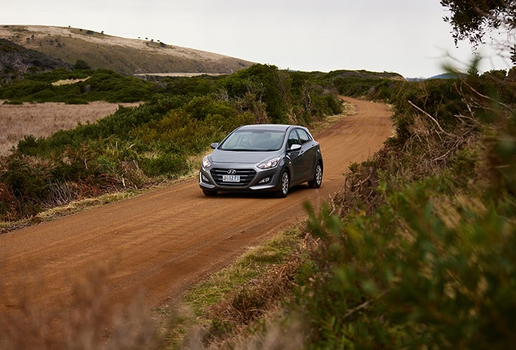Silver Hyundai driving on red dirt road