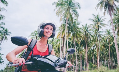 Person riding scooter along road lined with palm trees