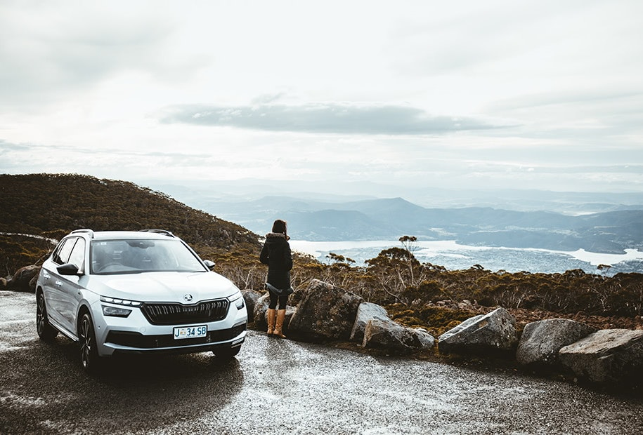 Car parked against a mountain view backdrop.